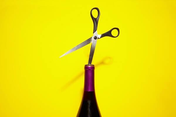 Use scissors to open a wine bottle